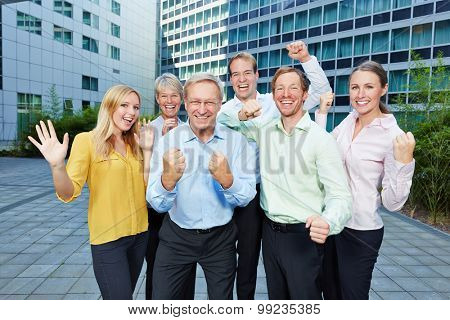 Winners cheering together with their clenched fists in a business team