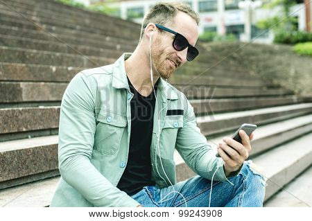 Man listening to the music with earbuds from a smart phone