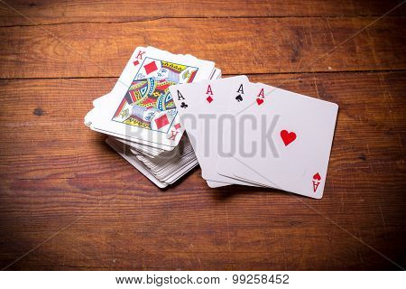 Deck of playing cards with ace cards on top.