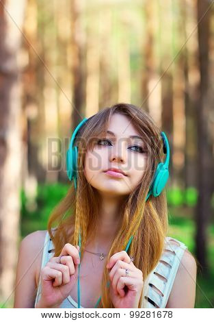 Beautiful girl listening to music with headphones at the park