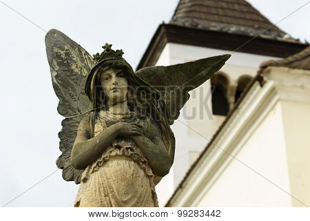 Statue of angel with broken wing on a cemetary poster