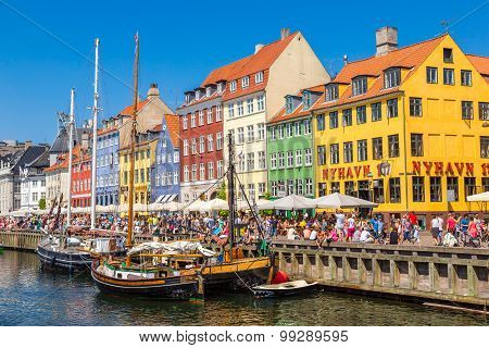 COPENHAGEN DENMARK - JULY 25 2014: Nyhavn district is one of the most famous landmark in Copenhagen. People enjoy sunny weather in open cafees in Copenhagen poster