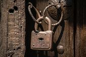 Old weathered grunge rusty locked padlock with rings on old wooden board door poster