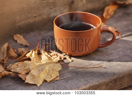 cup with hot drink on a wooden background autumn