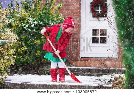 Little Girl Shoveling Snow In Winter