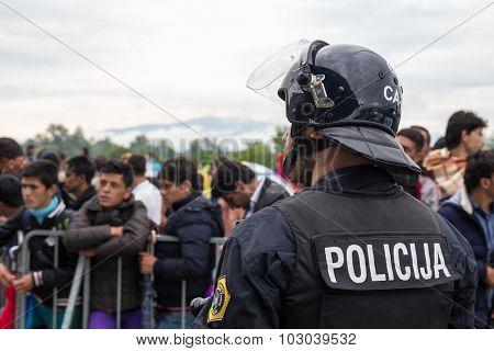 BREGANA, SLOVENIA: SEPTEMBER 19, 2015: Close up of policeman in front of group of immigrants and refugees from Middle East and North Africa at Bregana, state border between Slovenia and Croatia.