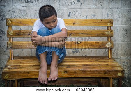 An Asian boy sitting in the park alone. He is homeless and scared, he is at high risk of being trafficked and abused poster