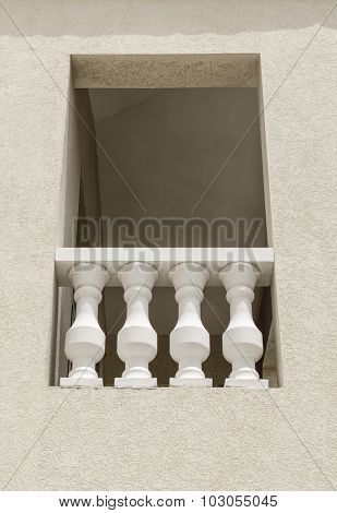 Close up of a narrow window with classic balusters. Building exterior details.