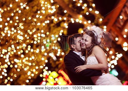 Bride And Groom Embracing At Night With Beautiful Lights In The Background