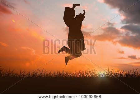 Happy male student in graduate robe jumping against orange and blue sky with clouds
