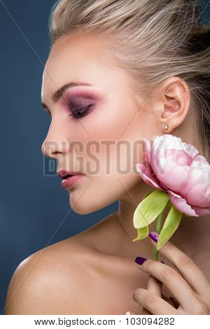 Side view portrait of attractive blonde woman with sensitive makeup holding peony near her face on blue background close up. Fashion photo.