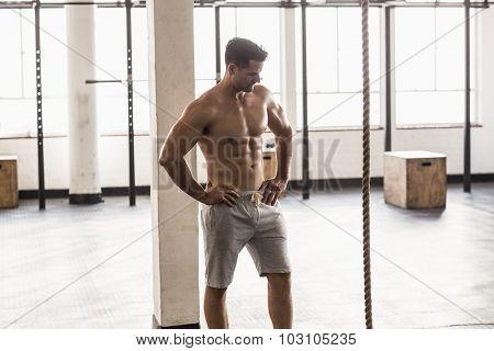 Serious muscular shirtless man posing in crossfit gym