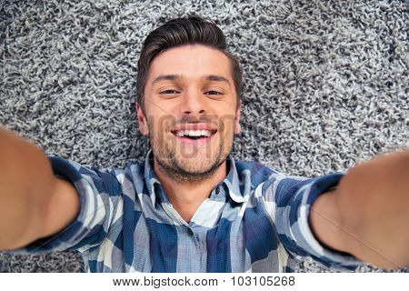 Portrait of a smiling man lying on the floor and making selfie photo