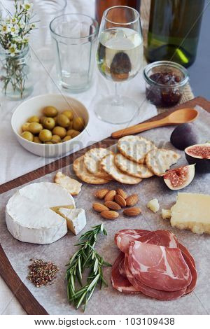 Selection of gourmet cured meat charcuterie salami, coppa, with brie camembert gruyere cheese served with olives nuts and fruit