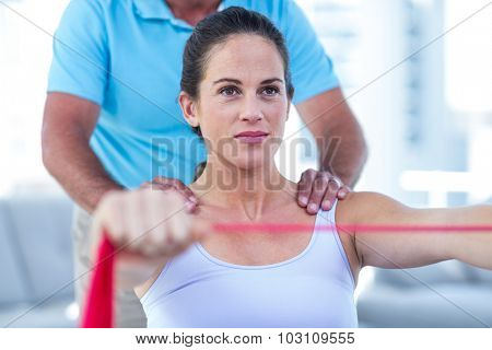Focused pregnant woman stretching exercise band