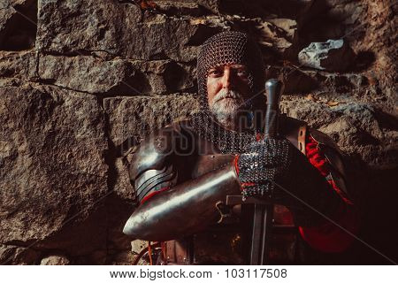 Old Medieval King In Armor With Sword On The Rocks Background