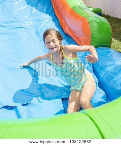 Smiling little girl playing on an inflatable slide bounce house
