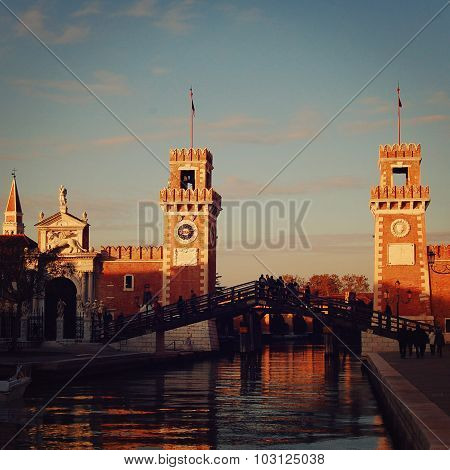 View of the Entrance to the Venetian Arsenal on sunset. Aged photo. Autumn evening in Venice. People crossing wooden bridge near Arsenal entrance. poster