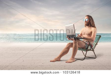 Surfer using a laptop at the beach