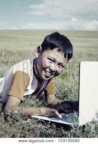 Mongolian Boy Laptop Grass Technology Connection Concept