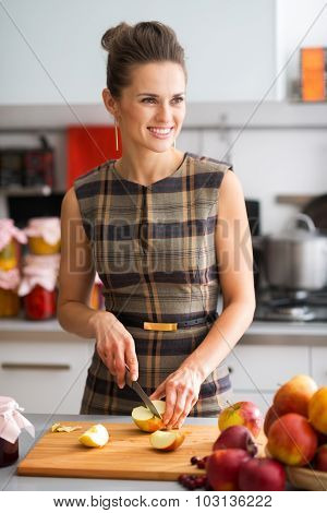 Woman Smiling Looking Into Distance While Cutting Apples