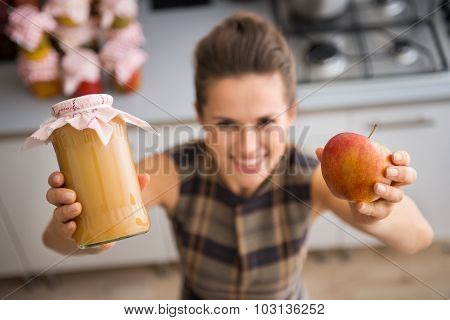 Closeup Of Woman's Hands Holding Apple Sauce And Fresh Apple