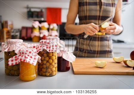 Preserved Fruit In Glass Jars With Woman Quartering Apple