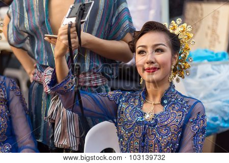 BANGKOK, THAILAND, February 17, 2015: A Thai lady  is checking her makeup make up on a mirror before the show celebrating the new Krung Kasem floating market in Bangkok, Thailand