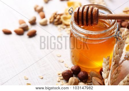 Honey in glass jar and nuts. Country breakfast concept