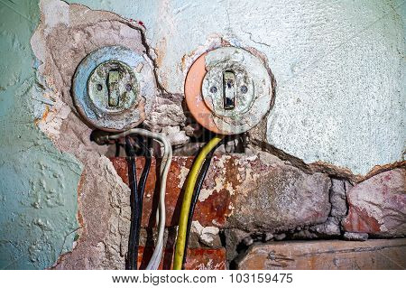 Two old electric switches in obsolete wall with wires, a lot of copy space