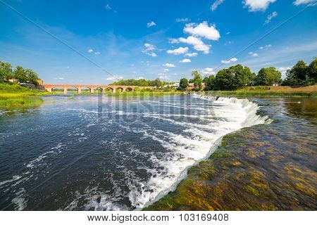 Landscape with old brick bridge over river Venta at Kuldiga, Latvia