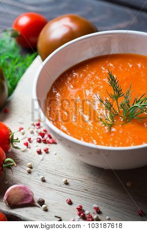 Tomato soup and fresh tomatoes on a wooden background