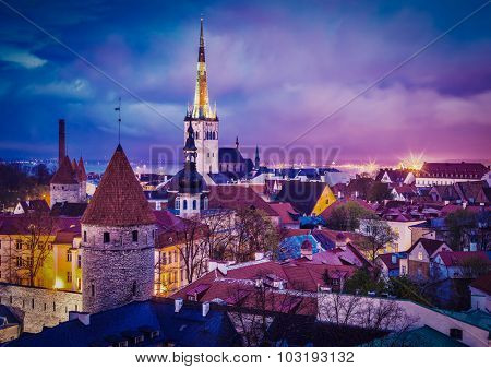 Vintage retro effect filtered hipster style image of Tallinn Medieval Old Town illuminated in evening twilight, with dramatic sky Estonia