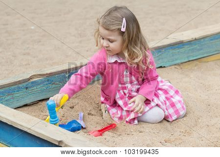 Little Blonde Girl Playing In Sandbox With Plastic Toy Tools