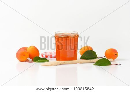 opened jar of apricot marmalade with wooden spoon and fresh apricots