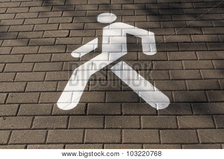 White Pedestrian Sign On Pavement.