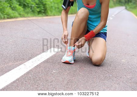 young woman runner tying shoelaces on trail