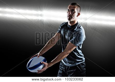 Focused rugby player looking away while holding ball against spotlight