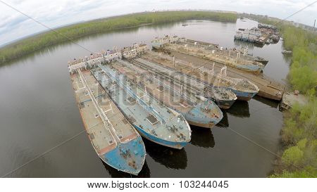 SAMARA - MAY 10, 2015: Moorage with few oil carriers in Volga river and city on horizon at spring cloudy day. Aerial view video frame