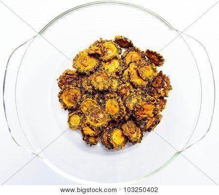 Tasty fried bittergourd chips kept on a glass bowl on a plain background