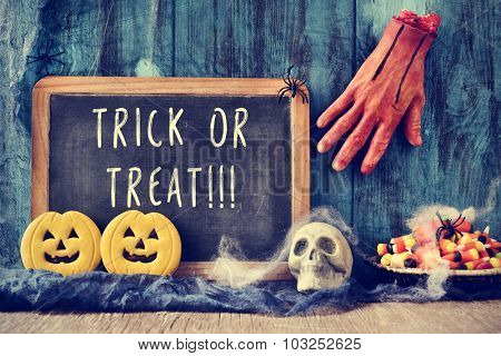 a chalkboard with the text trick or treat written in it in a dismal scene with an amputated hand, a skull, some pumpkin-shaped biscuits, some candies, spiders and cobwebs