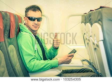 Young hipster man passenger satisfied with thumbs up after boarding - Concept of low coast flight and connection with modern technologies on board - Alternative lifestyle traveling around the world poster
