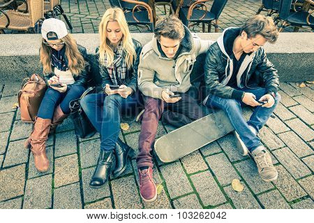 Group Of Young Hipster Friends Playing With Smartphone With Mutual Disinterest Towards Each Other