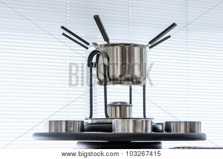 modern dishware, fondue set on window background