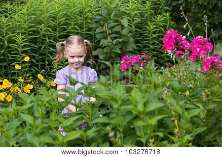 Little Girl With Tails Among Flowers In The Park