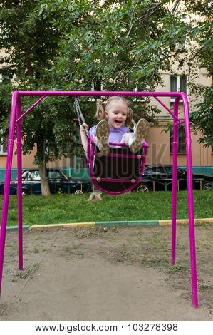 Little Girl With Pigtails On A Swing At Playground