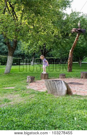Little Girl Jumping Between Stumps In The Park