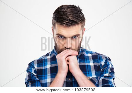 Portrait of a pensive casual man looking at camera isolated on a white background