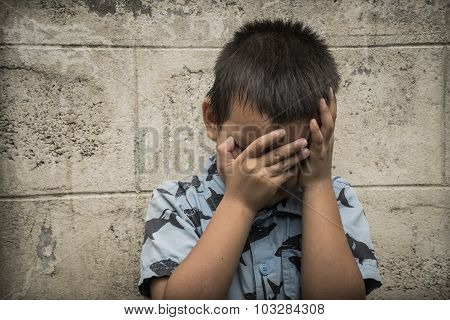 Young Asian boy covering his face with hands