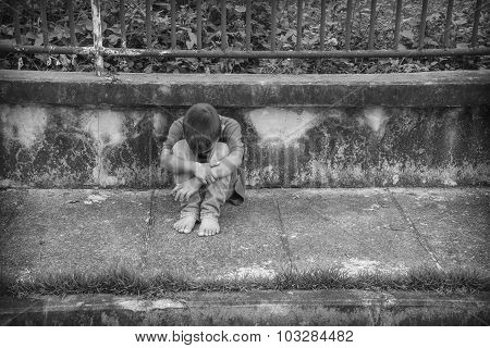 Young Asian homeless boy scared and alone